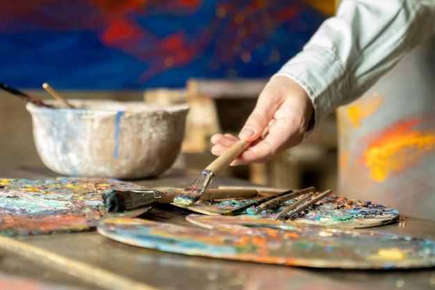 Main de femme artiste prend un pinceau sur une peinture. l'artiste crée une peinture