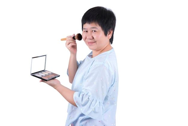 Main d'une femme asiatique d'âge moyen tenant un pinceau et des cosmétiques professionnels 8 nuances contour visage pouvoir fond de teint palette de maquillage isolé sur fond blanc