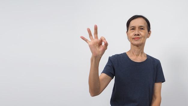 Main de femme asiatique âgée ou plus âgée faisant un signe de main ok ou ok sur fond blanc