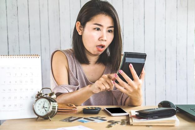 Main de femme asiatique choquée, comptant la dette