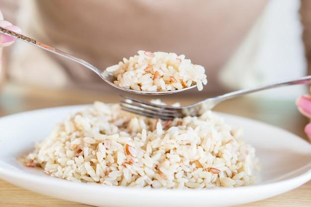 Main de femme asiatique manger du riz brun en bonne santé