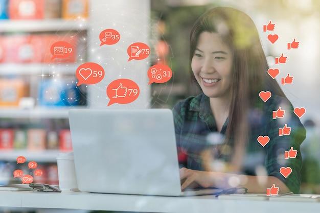 Main de femme asiatique utilisant un ordinateur portable pour vérifier l'application de réseau social avec le nombre de like,