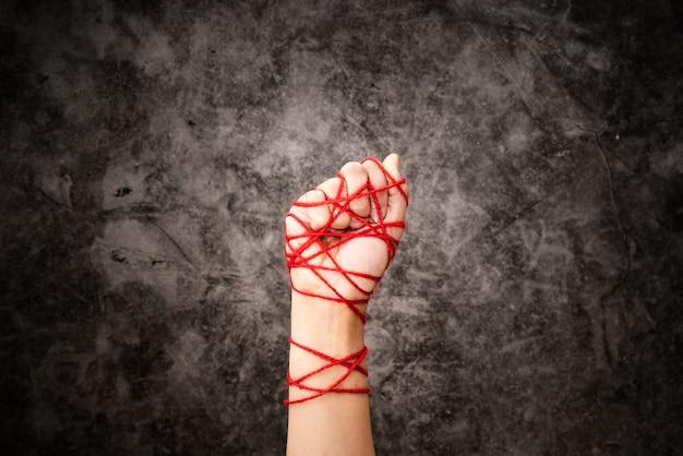 Main de femme attachée avec une corde, l'idée d'expression de la liberté sur un fond grunge sombre en low key.