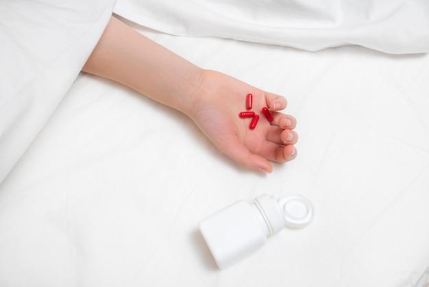 Main de femme avec beaucoup de drogues dans le lit