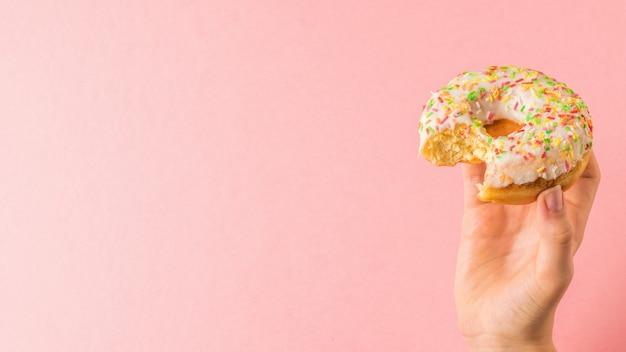 Main d'une femme avec un beignet mordu sur une surface rose