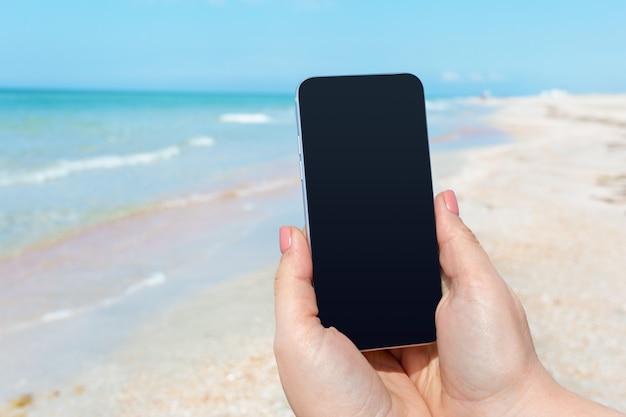 Main de femme belle à l'aide d'un téléphone intelligent à la plage