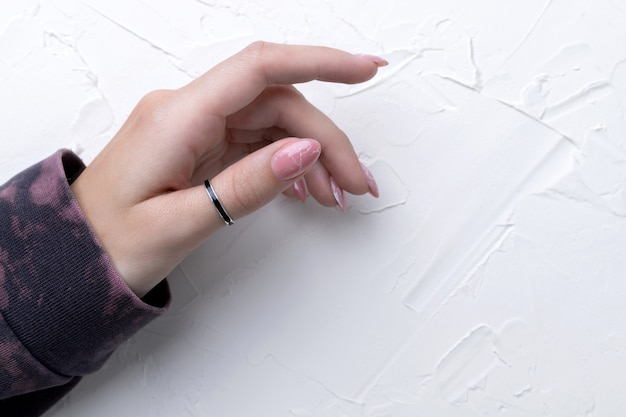 Main de femme bien entretenue dans un sweat à capuche rose tendance