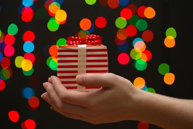 Main de femme avec boîte-cadeau, sur fond de guirlande
