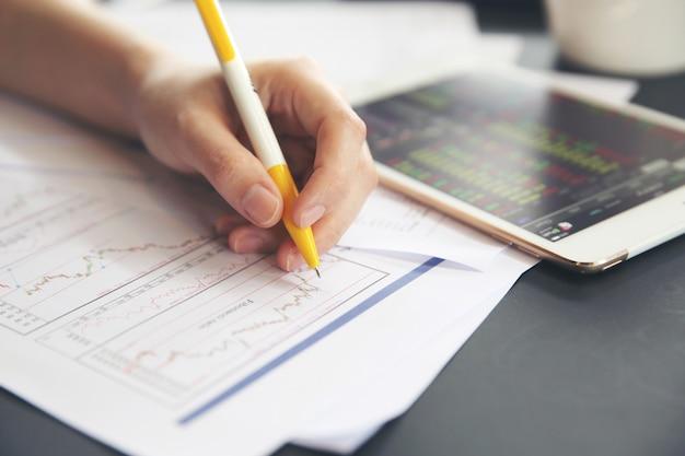 Main de femme de bureau travaillant sur le business papers et tablette