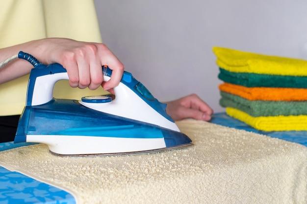 Main de femme caressant un tampon de serviettes sur une planche à repasser
