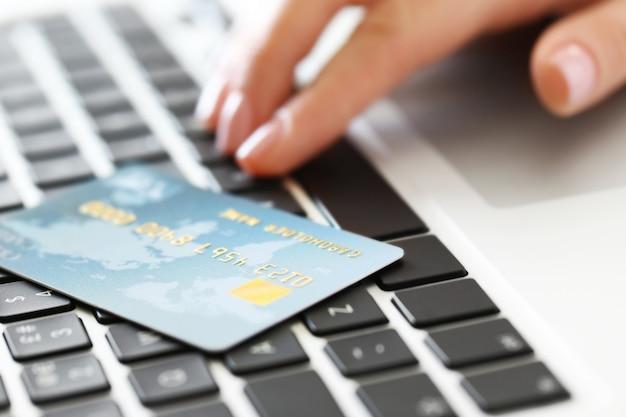 Main de femme et carte de crédit sur ordinateur portable, gros plan