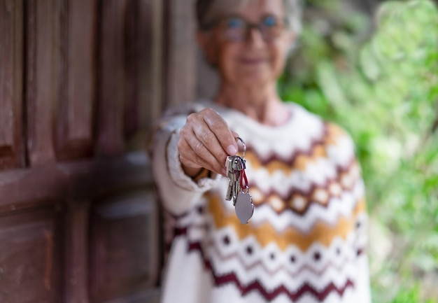 Main de femme caucasienne en pull d'hiver tenant les clés de la maison devant la porte en bois. affaires, banque, concept immobilier