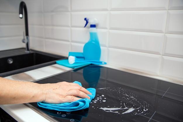 Une main de femme avec un chiffon en microfibre bleu frotte une plaque de vitrocéramique dans la cuisine.