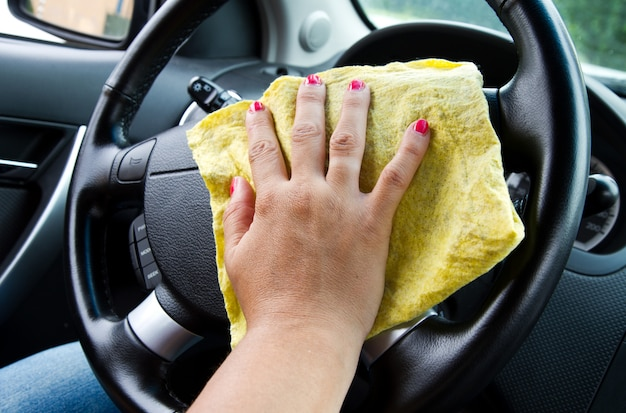 Main de femme avec chiffon en microfibre roue de polissage d'une voiture
