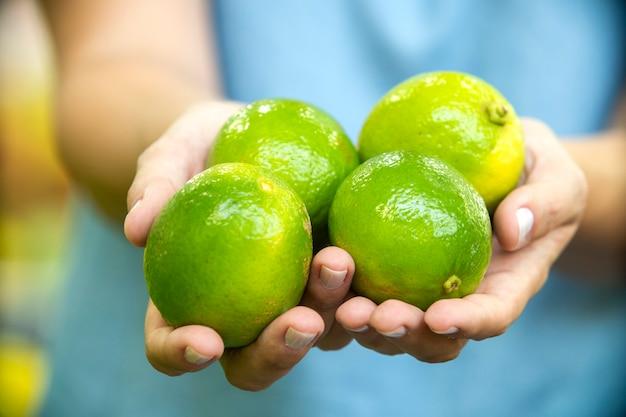 Main de femme choisissant des citrons au supermarché.