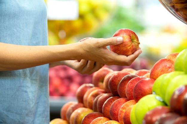 Main de femme choisissant la pomme rouge au supermarché.