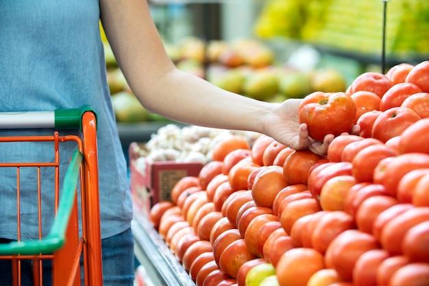 Main de femme choisissant des tomates au supermarché.