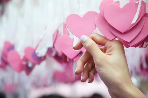 Une main de femme choisit le coeur rose lucky draw attaché à un ruban blanc sur un arbre dans une œuvre de charité