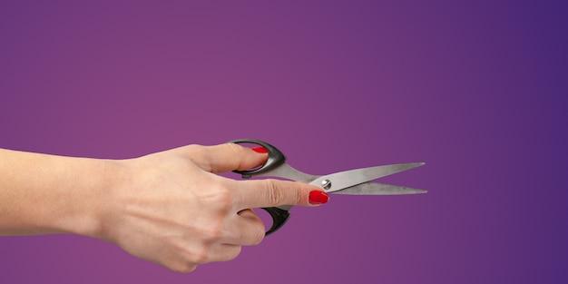 Main de femme avec des ciseaux