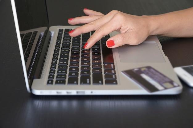 Main de femme sur clavier d'ordinateur portable avec carte de crédit et smartphone sur fond de table en bois, shopping concept en ligne.