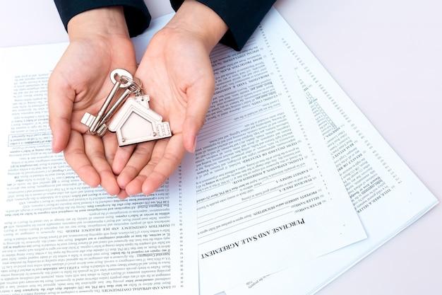 Main de femme et clé de la maison. contrat signé et clés de la propriété avec documents. concept pour de vrai e
