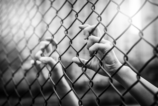 Main de femme sur une clôture grillagée.