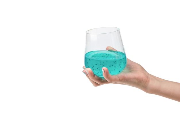Une main de femme avec un cocktail exotique isolé sur un blanc. une boisson exotique.