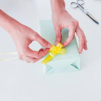 Main de femme collant le ruban jaune sur une boîte cadeau emballée sur un bureau blanc