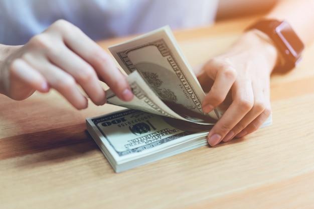 Main de femme comptant 100 dollars. le concept de dépenses en espèces.