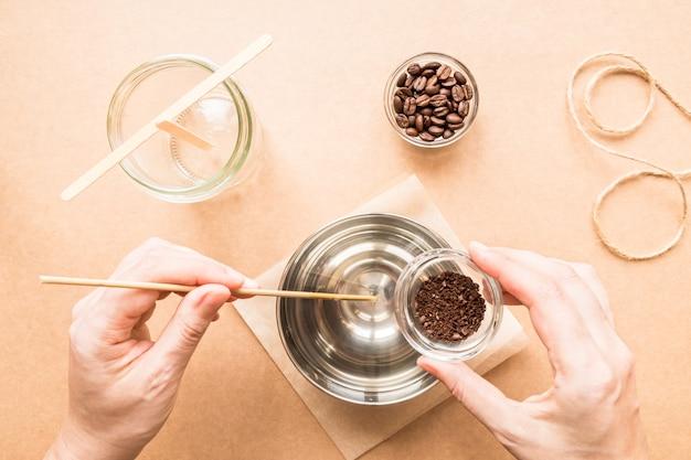 La main de la femme de concept de bricolage ajoute du café moulu à la cire et aux ingrédients pour fabriquer des bougies faites à la main