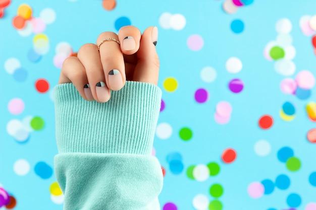 Main de femme avec des confettis colorés sur fond bleu. concept de salon de beauté mode spa
