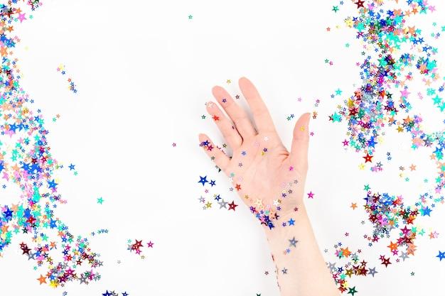 Main de femme avec confettis étoiles couleur festive