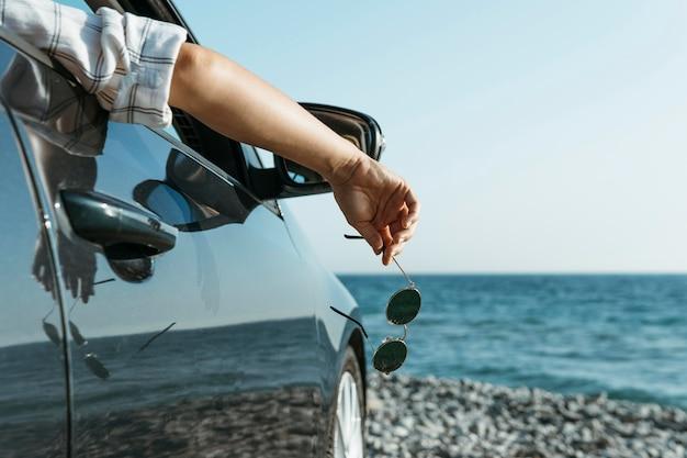Main de femme coup milieu suspendu à la fenêtre de la voiture près de la mer