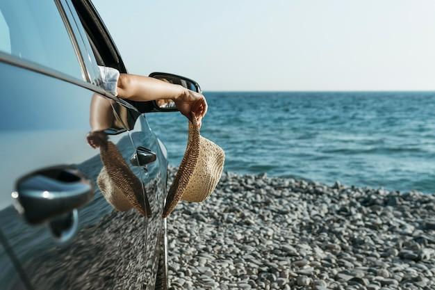 Main de femme coup milieu suspendu à la fenêtre de la voiture et tenant un chapeau près de la mer