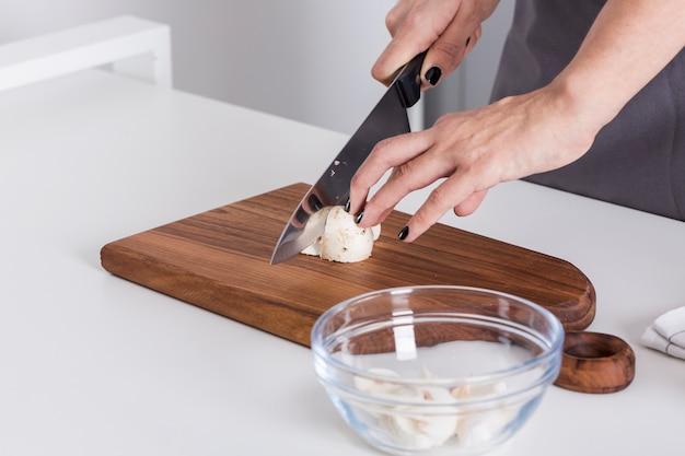 Main de femme coupant le champignon avec un couteau sur une planche à découper sur la table blanche