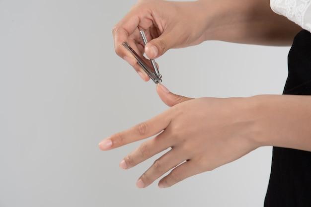 Main de femme coupant les ongles à l'aide d'un coupe-ongles sur fond gris