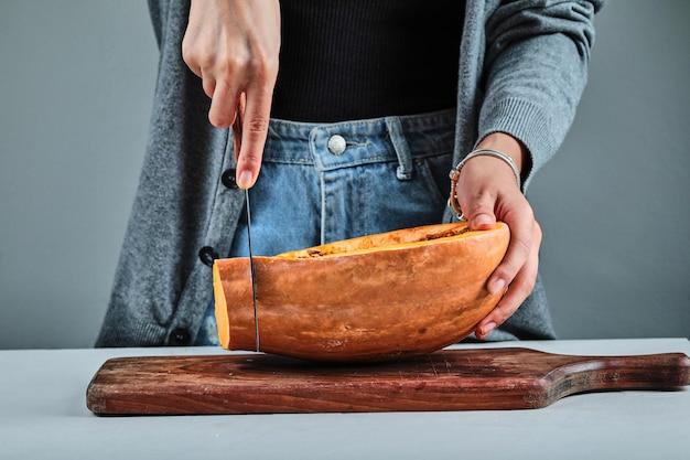 Une main de femme coupant une tranche de citrouille avec un couteau sur une planche de bois.