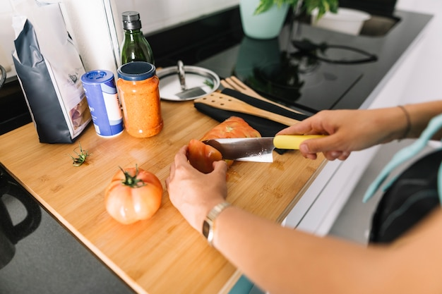 Main de femme coupant des tranches de tomate avec un couteau sur le comptoir de la cuisine