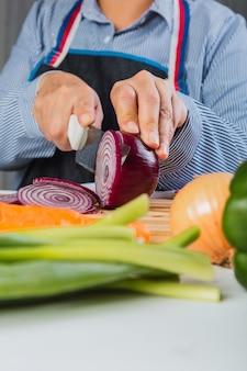 Main de femme couper les oignons rouges sur une planche à découper dans la cuisine à domicile