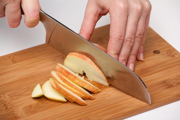Main de femme avec un couteau de cuisine broie une grosse pomme rouge sur une planche de bois