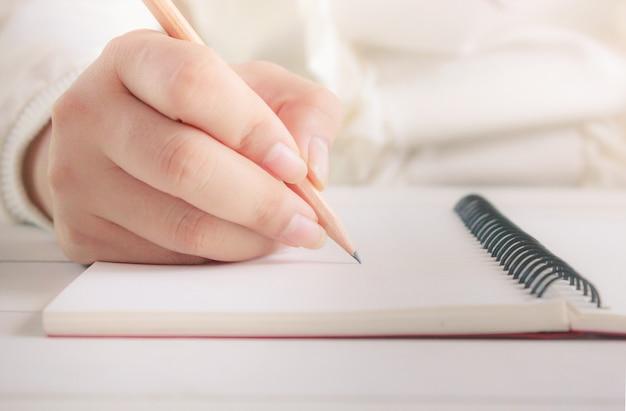 Main de femme avec un crayon écrit sur un cahier blanc.