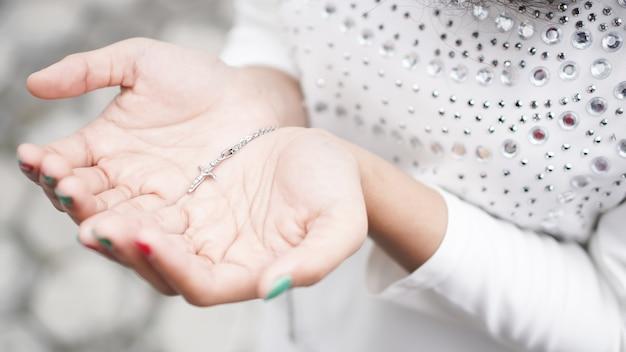 Main de femme avec une croix