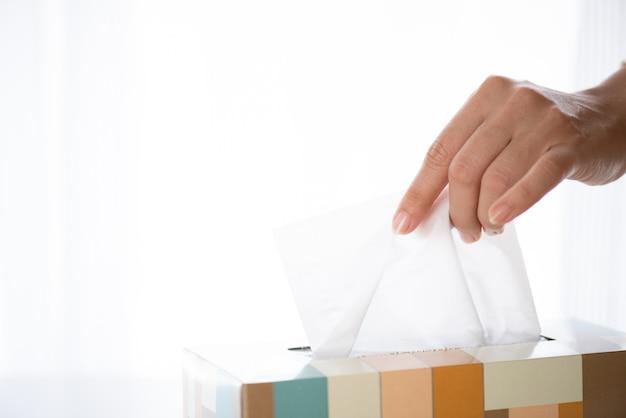 Main de femme cueillant du papier de soie blanc de la boîte de mouchoirs. concept de soins de santé.
