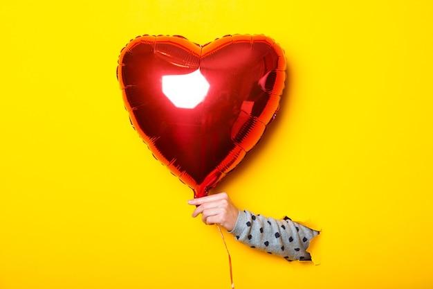 Main de femme dans un fond jaune déchiré tenant un coeur de ballon rouge gonflable à air.