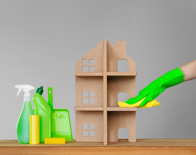 Une main de femme dans un gant de caoutchouc lave la maison symbolique avec un drap vert