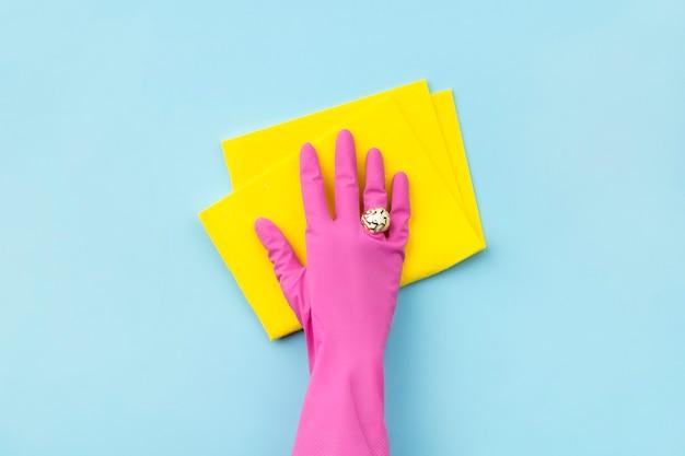 Main de femme dans un gant en caoutchouc rose essuyer par un chiffon sur fond bleu. service de nettoyage ou modèle de ménage.
