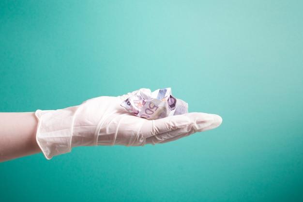 Main de femme dans un gant médical jetable blanc en caoutchouc est titulaire d'un projet de loi de 500 euros froissé fond vert copie espace