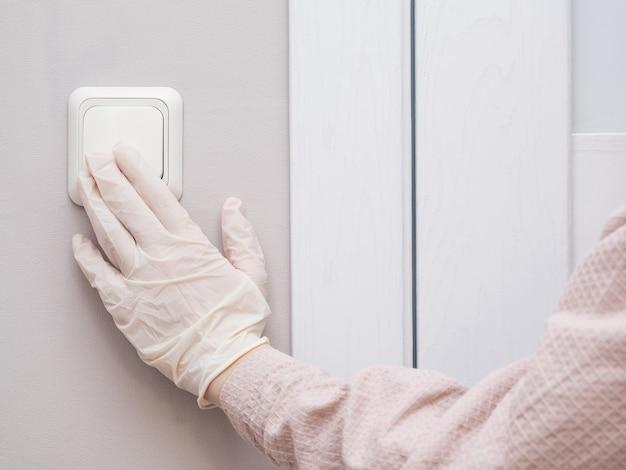 La main d'une femme dans des gants de caoutchouc stériles atteint l'interrupteur d'éclairage, copiez l'espace.