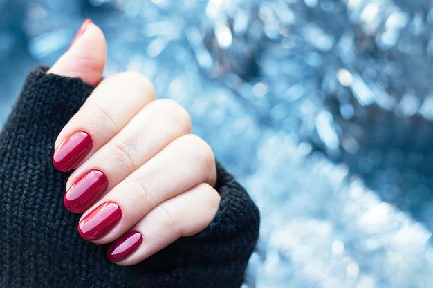 Main de femme dans des mitaines de gants tricotés avec des ongles rouge foncé brillant sur fond de guirlandes de noël