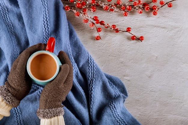 Main de femme dans des mitaines tenant une tasse de chocolat chaud